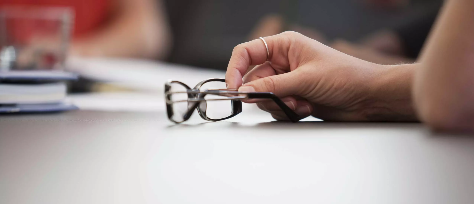 Person holding glasses on a table in a meeting